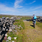 Cycling between stone walls.